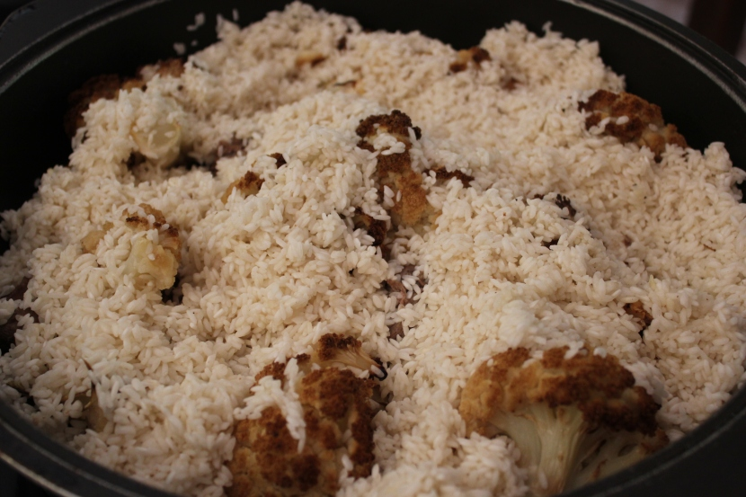 Cover the meat and cauliflower with the pre-soaked and browned rice